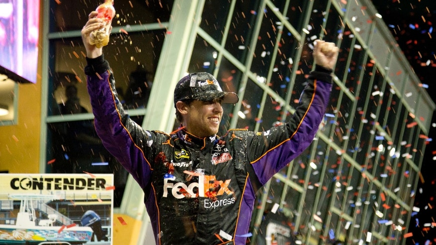 Denny Hamlin celebrates after winning the NASCAR Sprint Cup Series auto race in Homestead, Fla., Sunday, Nov. 17, 2013. (AP Photo/J Pat Carter)