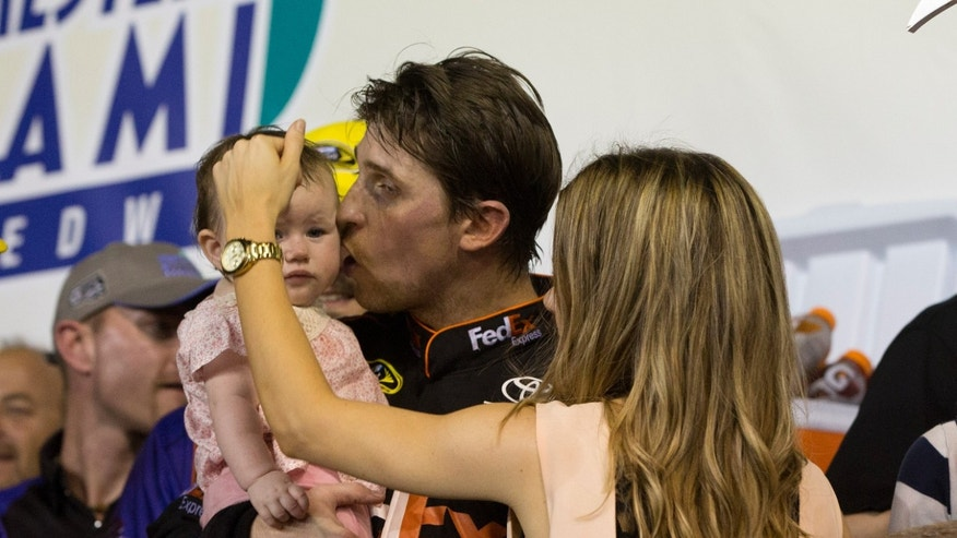 CORRECTS DENNY HAMLIN'S WIFE TO GIRLFRIEND AND ADDS LAST NAME, FISH - Denny Hamlin and his girlfriend, Jordan Fish, talk to their daughter, Taylor, as they celebrate winning the NASCAR Sprint Cup Series auto race in Homestead, Fla., Sunday, Nov. 17, 2013. (AP Photo/J Pat Carter)