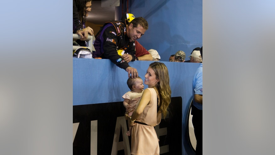 CORRECTS DENNY HAMLIN'S WIFE TO GIRLFRIEND AND ADDS LAST NAME, FISH - One of Denny Hamlin's crew talks to his girlfriend, Jordan Fish, and baby, Taylor, after Hamlin won the NASCAR Sprint Cup Series auto race in Homestead, Fla., Sunday, Nov. 17, 2013. (AP Photo/J Pat Carter)