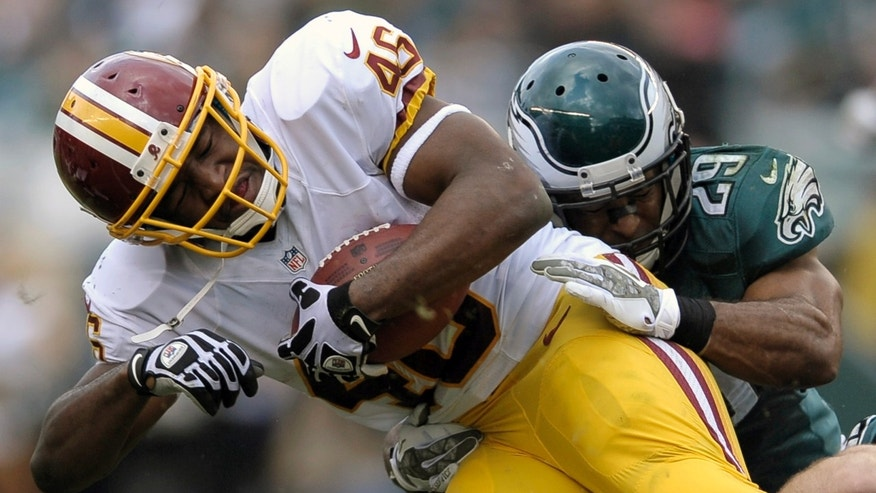 Washington Redskins running back Alfred Morris, left, is stopped by Philadelphia Eagles strong safety Nate Allen during the first half of an NFL football game in Philadelphia, Sunday, Nov. 17, 2013. (AP Photo/Michael Perez)