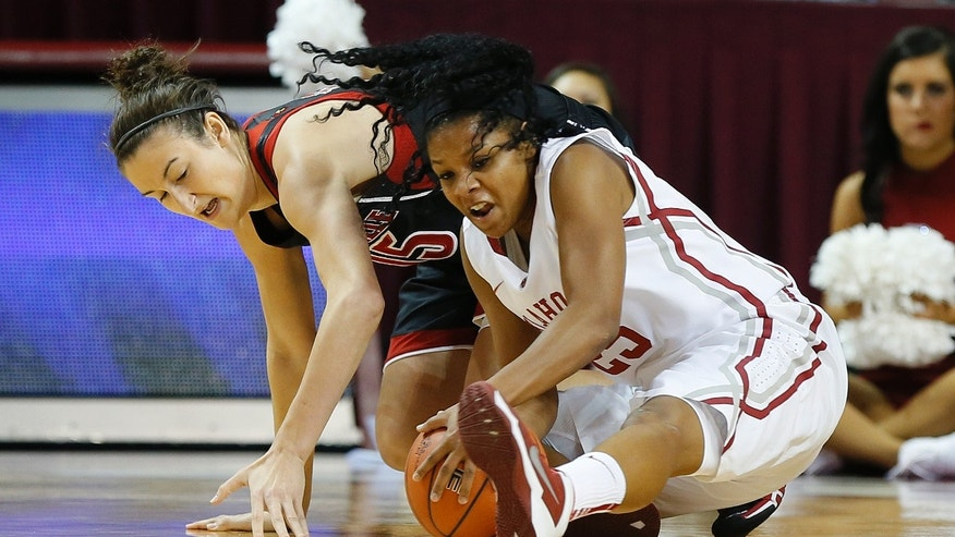 Oklahoma's Gioya Carter, right, gains control of the ball beside Louisville's Megan Deines during the first half of an NCAA college basketball game in Norman, Okla., Sunday, Nov. 17, 2013. (AP Photo/Bryan Terry)