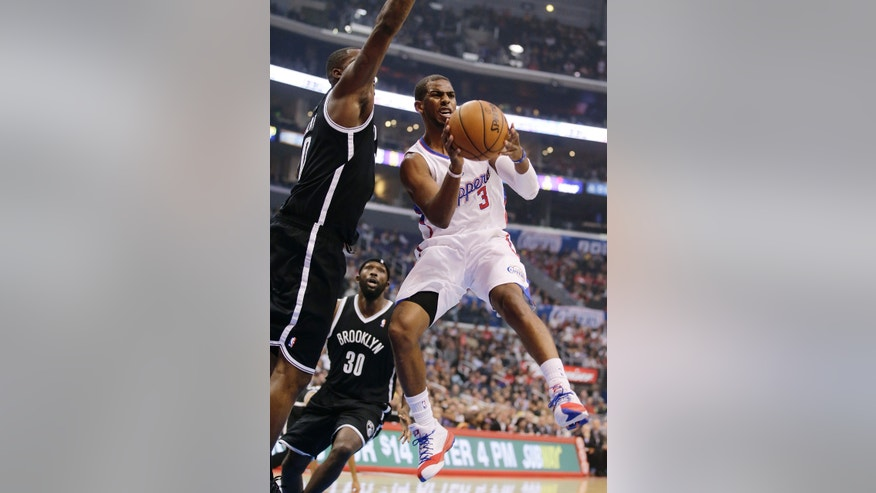 Los Angeles Clippers' Chris Paul, right, passes the ball as he is defended by Brooklyn Nets' Andray Blatche during the first half of an NBA basketball game on Saturday, Nov. 16, 2013, in Los Angeles. (AP Photo/Jae C. Hong)