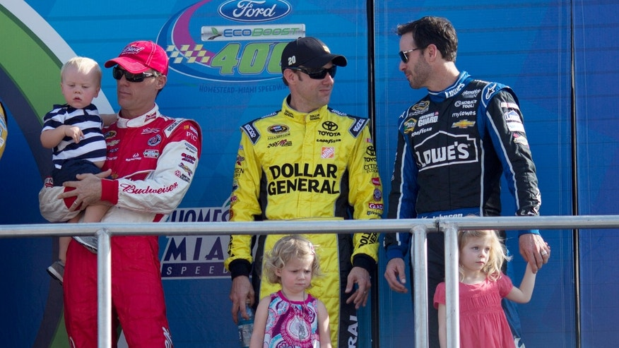Kevin Harvick, left, with his son, Keelan, Matt Kenseth, center, with his daughter, Grace, and Jimmie Johnson, right, with his daughter, Genevieve, look on during driver introductions before the NASCAR Sprint Cub Series auto race in Homestead, Fla., Sunday, Nov. 17, 2013. (AP Photo/J Pat Carter)