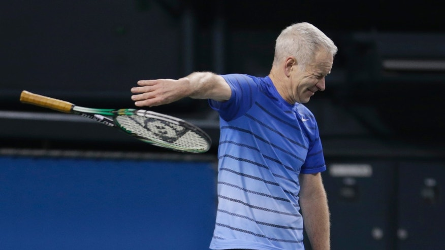 Former world No. 1 tennis player John McEnroe of the U.S. throws his racket after losing a point against Japan's Kei Nishikori during their charity tennis match in Tokyo, Sunday, Nov. 17, 2013. McEnroe, 54, gave Nishikori, 23, a run for his money in the charity match for the victims of the March 11, 2011 earthquake and tsunami. (AP Photo/Shizuo Kambayashi)