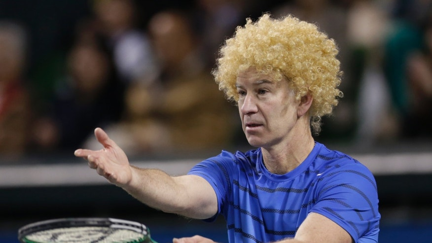 Former world No. 1 tennis player John McEnroe of the U.S. wearing a wig questions a call by the umpire during a charity tennis match against Japan's Kei Nishikori in Tokyo, Sunday, Nov. 17, 2013. McEnroe, 54, gave Nishikori, 23, a run for his money in the charity match for the victims of the March 11, 2011 earthquake and tsunami. (AP Photo/Shizuo Kambayashi)
