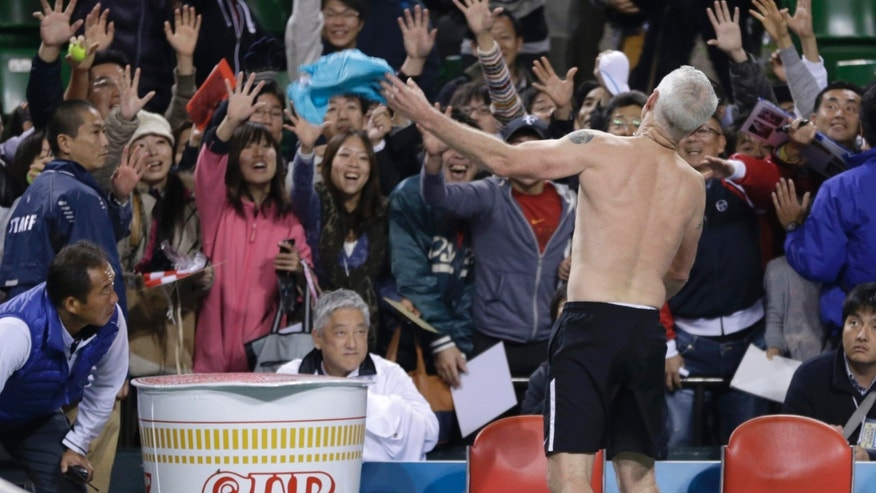 Former world No. 1 tennis player John McEnroe of the U.S. throws his shirt to spectators after his charity tennis match against Japan's Kei Nishikori in Tokyo, Sunday, Nov. 17, 2013. McEnroe, 54, gave Nishikori, 23, a run for his money in the charity match for the victims of the March 11, 2011 earthquake and tsunami. (AP Photo/Shizuo Kambayashi)
