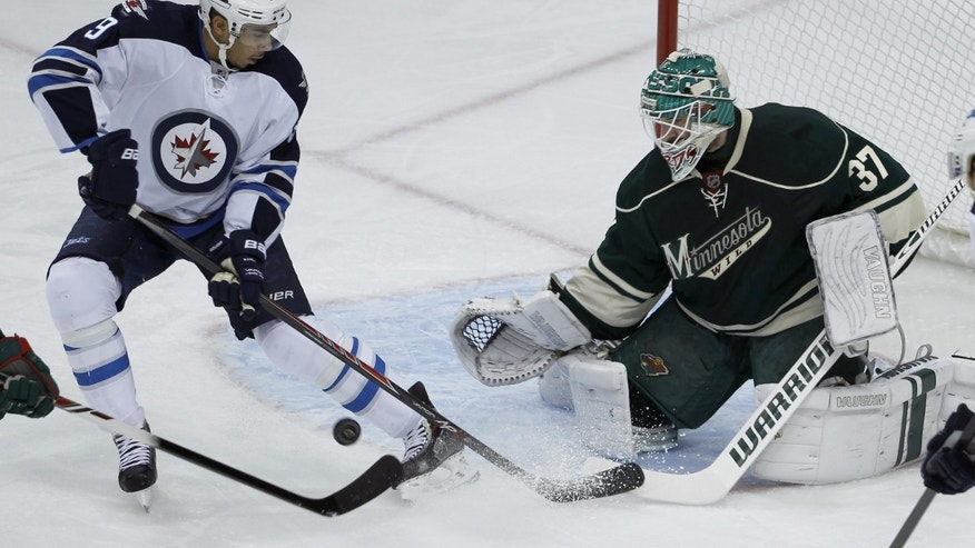Minnesota Wild goalie Josh Harding (37) deflects a shot by Winnipeg Jets left wing Evander Kane during the first period of an NHL hockey game in St. Paul, Minn., Sunday, Nov. 17, 2013. (AP Photo/Ann Heisenfelt)
