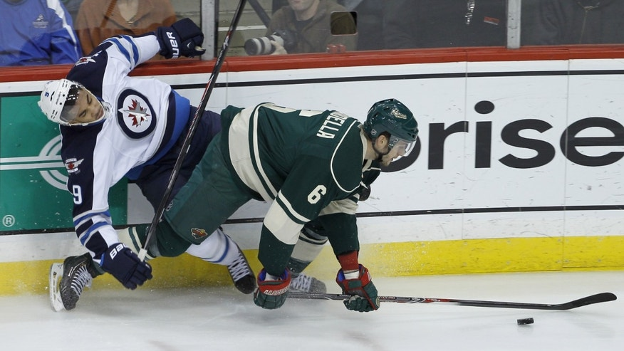Minnesota Wild defenseman Marco Scandella (6) and Winnipeg Jets left wing Evander Kane falls while chasing the puck during the first period of an NHL hockey game in St. Paul, Minn., Sunday, Nov. 17, 2013. (AP Photo/Ann Heisenfelt)