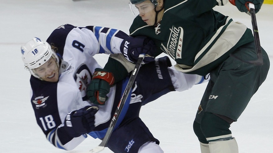 Winnipeg Jets center Bryan Little (18) takes a hit from Minnesota Wild center Charlie Coyle (3) during the first period of an NHL hockey game in St. Paul, Minn., Sunday, Nov. 17, 2013. (AP Photo/Ann Heisenfelt)