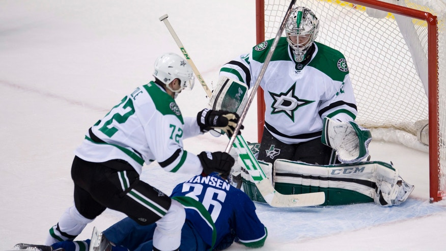 Dallas Stars right wing Erik Cole (72) stops Vancouver Canucks right wing Jannik Hansen (36) from getting a shot on Stars goalie Kari Lehtonen (32) during second period NHL action in Vancouver, British Columbia, Sunday, Nov. 17, 2013. (AP Photo/The Canadian Press, Jonathan Hayward)