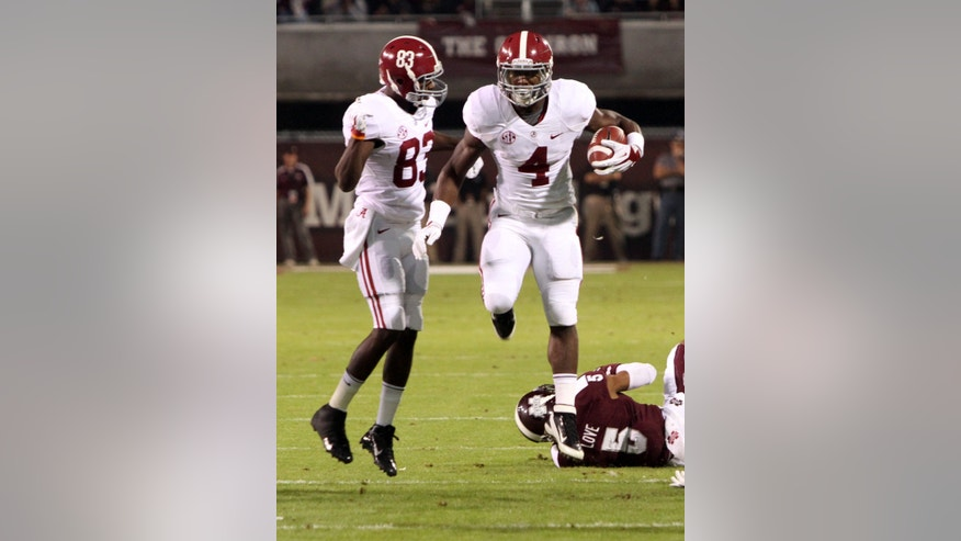 Alabama running back T.J. Yeldon (4) leaps past Mississippi State defensive back Jamerson Love (5) and runs past teammate wide receiver Kevin Norwood (83) for a gain during the first half of an NCAA college football game, Saturday, Nov. 16, 2013, in Starkville, Miss. (AP Photo/Kerry Smith)