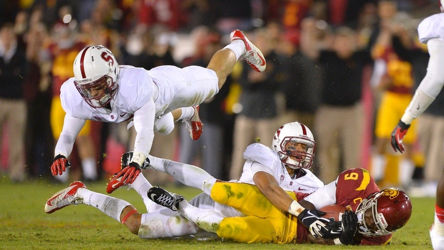 Southern California wide receiver Marqise Lee, right, is tackled by Stanford defensive back Usua Amanam, center, as safety Ed Reynolds jumps over during the second half of an NCAA college football game, Saturday, Nov. 16, 2013, in Los Angeles. Lee was injured on the play and left the game. USC won 20-17. (AP Photo/Mark J. Terrill)