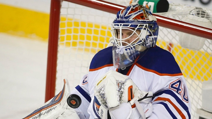 Edmonton Oilers goalie Devan Dubnyk deflects the puck during the first period of an NHL hockey game Saturday, Nov. 16, 2013 in Calgary, Alberta. (AP Photo/The Canadian Press, Jeff McIntosh)