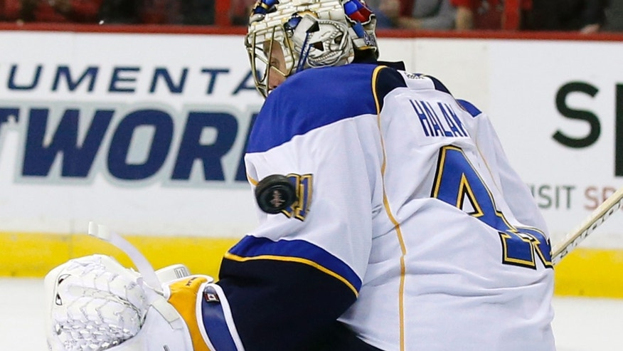 The puck bounces off the shoulder of St. Louis Blues goalie Jaroslav Halak (41) for a goal in the first period of an NHL hockey game against the Washington Capitals, Sunday, Nov. 17, 2013, in Washington. (AP Photo/Alex Brandon)
