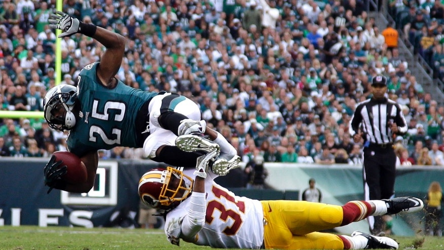 Philadelphia Eagles running back LeSean McCoy (25) is upended by Washington Redskins strong safety Brandon Meriweather during the first half of an NFL football game in Philadelphia, Sunday, Nov. 17, 2013. (AP Photo/Matt Slocum)