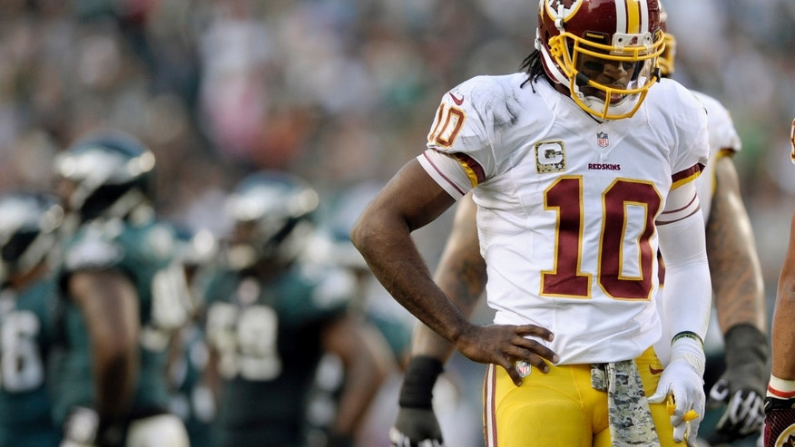 Washington Redskins quarterback Robert Griffin III walks across the field after a play during the second half of an NFL football game against the Philadelphia Eagles in Philadelphia, Sunday, Nov. 17, 2013. (AP Photo/Michael Perez)