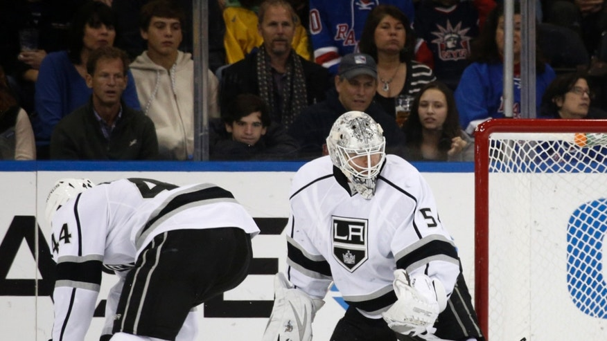 The puck glances off the skate of Los Angeles Kings goalie Ben Scrivens (54) as Los Angeles Kings defenseman Robyn Regehr (44) of Brazil loses his balance in the first period of their NHL hockey game at Madison Square Garden in New York, Sunday, Nov. 17, 2013.  (AP Photo/Kathy Willens)