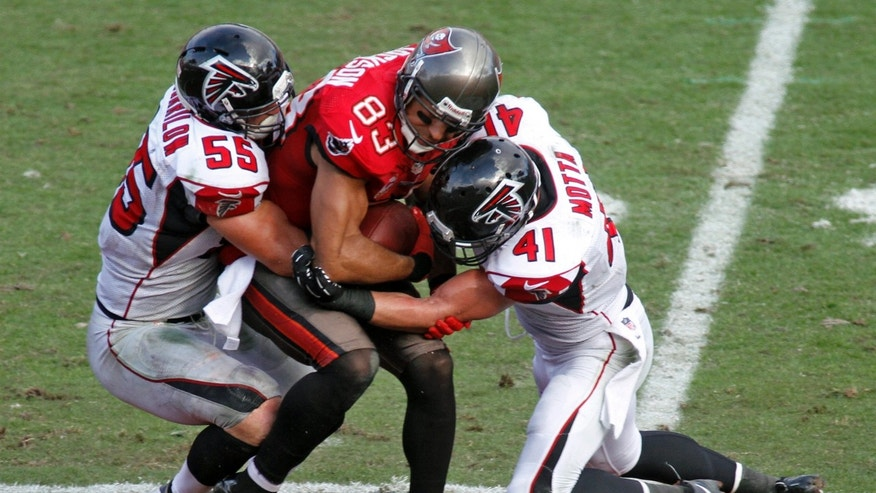 Tampa Bay Buccaneers wide receiver Vincent Jackson (83) is sandwiched by Atlanta Falcons outside linebacker Paul Worrilow (55) and strong safety Zeke Motta (41) after a reception during the fourth quarter of an NFL football game on Sunday, Nov. 17, 2013, in Tampa, Fla. (AP Photo/Reinhold Matay)