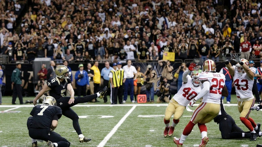 New Orleans Saints kicker Garrett Hartley (5) kicks the game winning field goal as  Luke McCown holds at the end of regulation in the second half of an NFL football game against the San Francisco 49ers in New Orleans, Sunday, Nov. 17, 2013.  The Saints won 23-20. (AP Photo/Dave Martin)