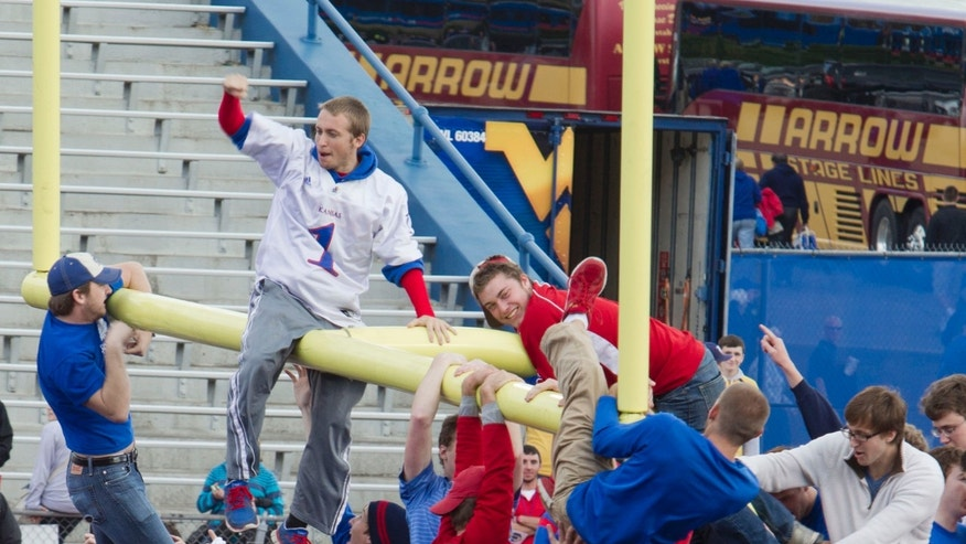 Kansas fans climb the goal post after their 31-19 win over West Virginia in an NCAA college football game at Kansas Memorial Stadium in Lawrence, Kan., Saturday, Nov. 16, 2013. (AP Photo/The Kansas City Star, Shane Keyser)