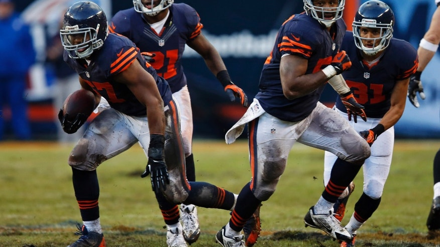 Chicago Bears linebacker Jon Bostic , left, runs after intercepting a pass thrown by Baltimore Ravens quarterback Joe Flacco during the first half of an NFL football game, Sunday, Nov. 17, 2013, in Chicago. (AP Photo/Charles Rex Arbogast)