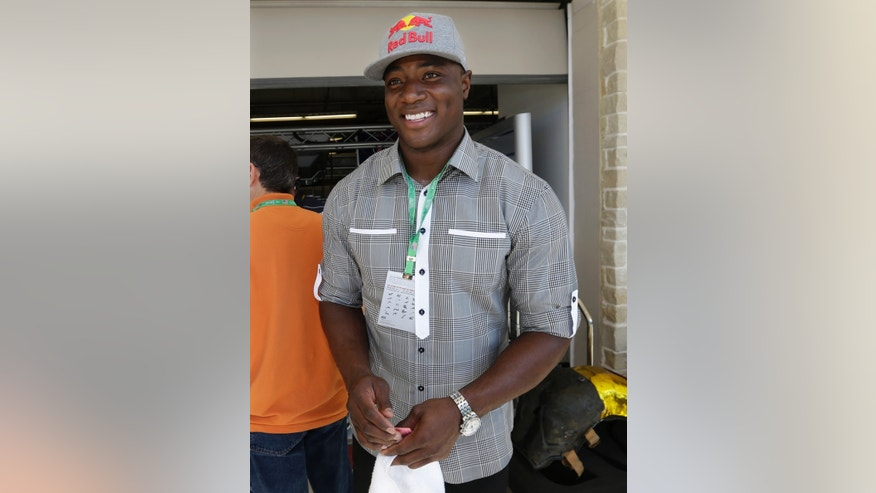 Dallas Cowboys' DeMarcus Ware walks through the pits before the Formula One U.S. Grand Prix auto race at the Circuit of the Americas, Sunday, Nov. 17, 2013, in Austin, Texas. (AP Photo/Darron Cummings)