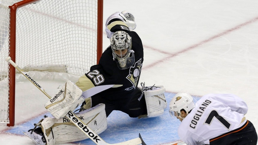 Pittsburgh Penguins goalie Marc-Andre Fleury (29) blocks a shot by Anaheim Ducks' Andrew Cogliano (7) in the first period of a NHL hockey game in Pittsburgh Monday, Nov. 18, 2013.(AP Photo/Gene J. Puskar)