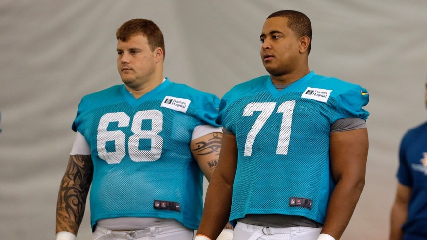 July 24, 2013: Miami Dolphins guard Richie Incognito (68) and tackle Jonathan Martin (71) stand on the field during an NFL football practice in Davie, Fla. (AP/Lynne Sladky, File)