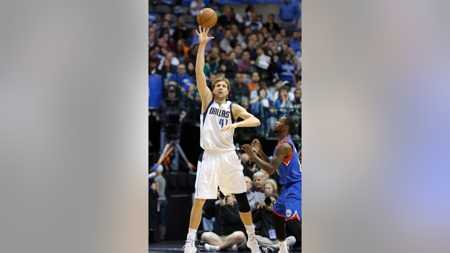 Dallas Mavericks power forward Dirk Nowitzki (41) of Germany stretches to catch a pass against Philadelphia 76ers guard Tony Wroten (8) during the first half of an NBA basketball game in Dallas,  Monday, Nov. 18, 2013. (AP Photo/LM Otero)