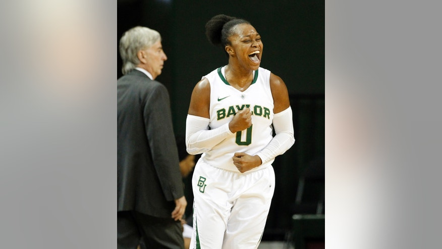 Baylor guard Odyssey Sims (0) celebrates shooting a 3-point basket  as Rice head coach Greg Williams, rear, stands by the team bench in the first half of an NCAA college basketball game, Monday, Nov. 18, 2013, in Waco, Texas. (AP Photo/Tony Gutierrez)