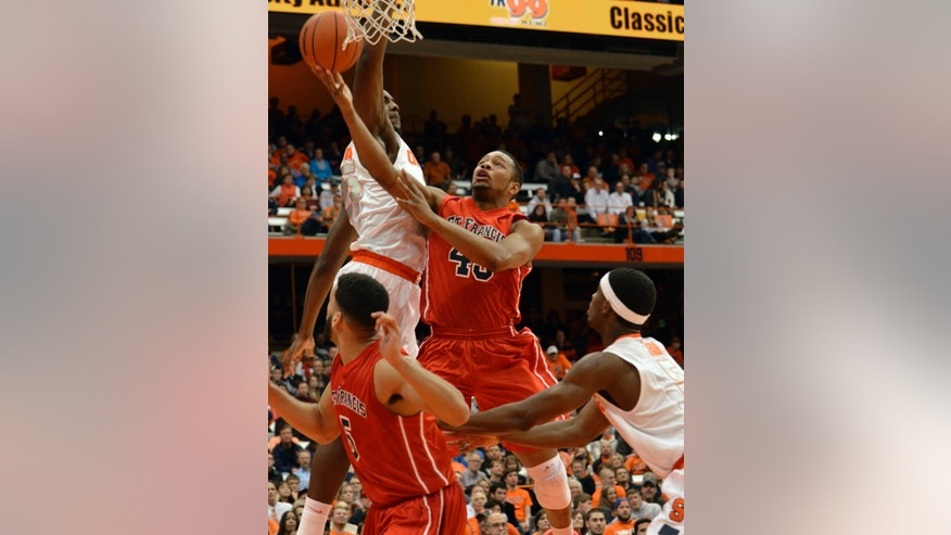 St. Francis' Wayne Martin scores between Syracuse's Rakeem Christmas, left, and C. J. Fair during the first half of an NCAA college basketball game in Syracuse, N.Y., Monday, Nov. 18, 2013. (AP Photo/Kevin Rivoli)
