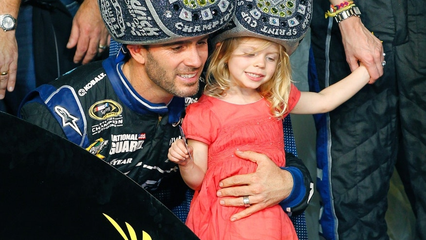 Jimmie Johnson and his daughter, Genevieve, wear championship ring hats as they celebrate him winning his sixth NASCAR Sprint Cup Series auto race title in eight years in Homestead, Fla., Sunday, Nov. 17, 2013. (AP Photo/Terry Renna)