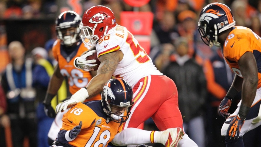 Denver Broncos quarterback Peyton Manning (18) hits Kansas City Chiefs inside linebacker Derrick Johnson (56) low after Johnson recovered a fumble in the first quarter of an NFL football game, Sunday, Nov. 17, 2013, in Denver. (AP Photo/Joe Mahoney)