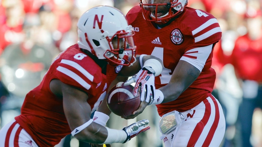 Nebraska quarterback Tommy Armstrong Jr. (4) hands off the ball to running back Ameer Abdullah (8) in the first half of an NCAA college football game against Michigan State in Lincoln, Neb., Saturday, Nov. 16, 2013. (AP Photo/Nati Harnik)
