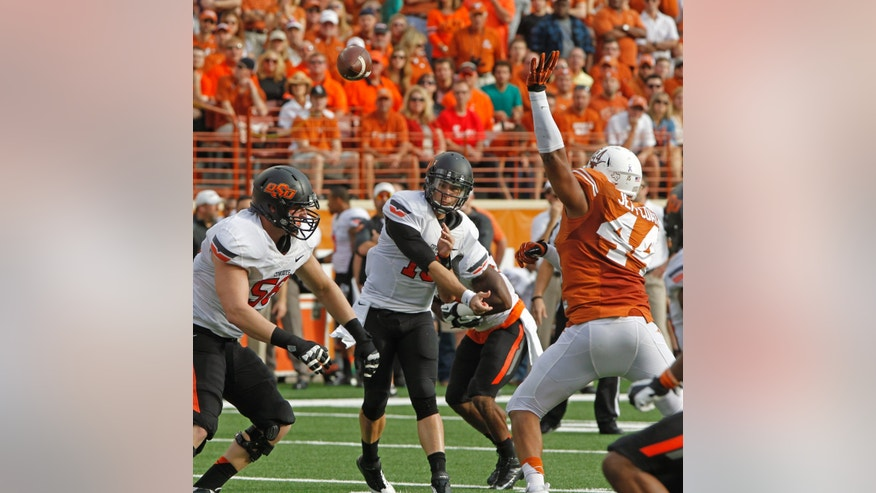 Oklahoma State quarterback Clint Chelf (10) passes against Texas defensive end Jackson Jeffcoat (44) during the first quarter of an NCAA college football game Saturday, Nov. 16, 2013, in Austin, Texas. Oklahoma State won 38-13. (AP Photo/Michael Thomas)