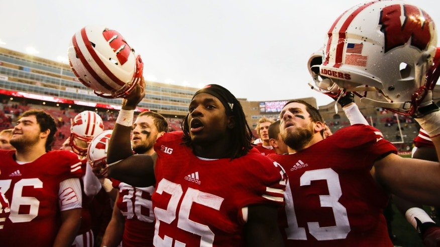 Wisconsin's Melvin Gordon (25) signs with his teammates after they beat Indiana 51-3 in an NCAA college football game Saturday, Nov. 16, 2013, in Madison, Wis. (AP Photo/Andy Manis)