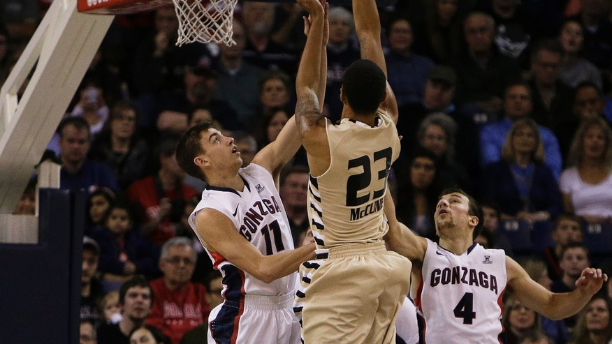 Oakland's Tommy McCune (23) attempts a jump shot against Gonzaga's David Stockton (11) and Kevin Pangos (4) during the first half of an NCAA basketball game, in Spokane, Wash., on Sunday, Nov. 17, 2013. (AP Photo/Young Kwak)
