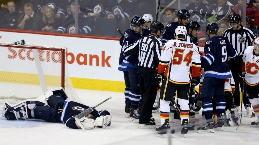 Winnipeg Jets' goaltender Al Montoya (35) lays on the ice after being crushed by Calgary Flames' Lee Stempniak (22) during third period NHL hockey action in Winnipeg Monday, Nov. 18, 2013. (AP Photo/The Canadian Press, Trevor Hagan)