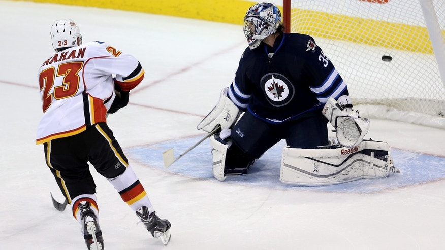 Calgary Flames' Sean Monahan (23) scores the shootout winner against Winnipeg Jets' goaltender Al Montoya (35) during NHL hockey action in Winnipeg Monday, Nov. 18, 2013. (AP Photo/The Canadian Press, Trevor Hagan)