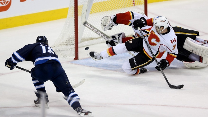Winnipeg Jets' Bryan Little (18) scores a goal to tie the game with 5.6 seconds left against Calgary Flames' goaltender Reto Berra (29) and TJ Brodie (7) during third period NHL hockey action in Winnipeg Monday, Nov. 18, 2013. (AP Photo/The Canadian Press, Trevor Hagan)