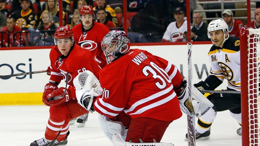 Carolina Hurricanes goalie Cam Ward (30) eyes the puck as teammate Chris Terry (58) and Boston Bruins' Patrice Bergeron (37) give chase during the first period of an NHL hockey game in Raleigh, N.C., Monday, Nov. 18, 2013. (AP Photo/Karl B DeBlaker)