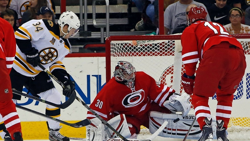 Carolina Hurricanes goalie Cam Ward (30) blocks the shot of Boston Bruins' Carl Soderberg (34) of Germany, with Hurricanes' Eric Staal (12) looking on during the second period of an NHL hockey game in Raleigh, N.C., Monday, Nov. 18, 2013. (AP Photo/Karl B DeBlaker)