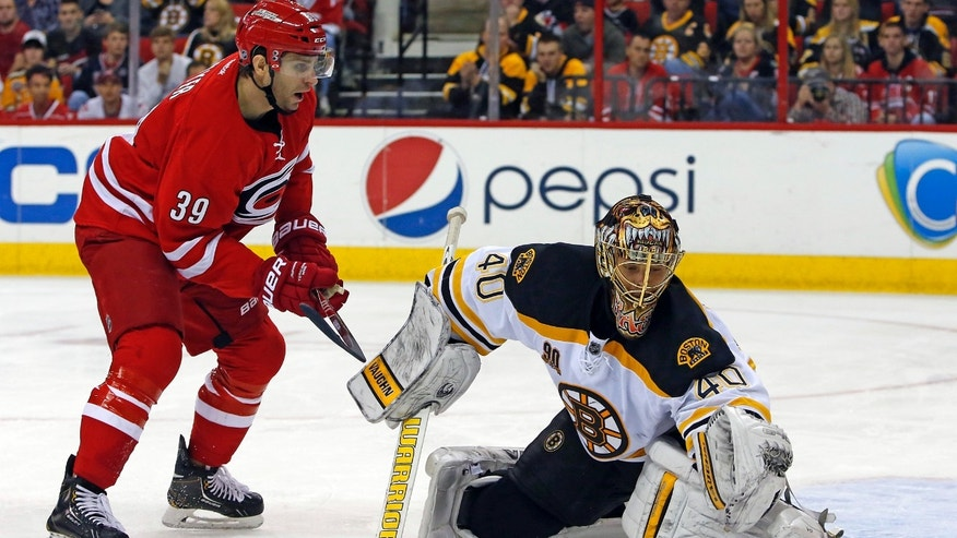 Boston Bruins goalie Tuukka Rask (40) of Finland, blocks the shot of Carolina Hurricanes' Patrick Dwyer (39) during the second period of an NHL hockey game in Raleigh, N.C., Monday, Nov. 18, 2013. (AP Photo/Karl B DeBlaker)