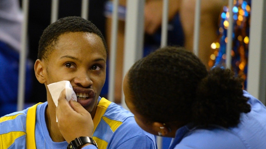 Southern University guard Tre Lynch (30) has his lip attended to by a trainer during the second half of an NCAA college basketball game against Florida Monday, Nov. 18, 2013 in Gainesville, Fla. Florida won the game 67-53.(AP Photo/Phil Sandlin)