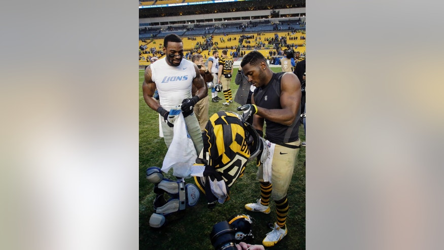 Pittsburgh Steelers wide receiver Antonio Brown, right, and Detroit Lions wide receiver Calvin Johnson, left, exchange jerseys after an NFL football game in Pittsburgh, Sunday, Nov. 17, 2013. (AP Photo/Gene J. Puskar)