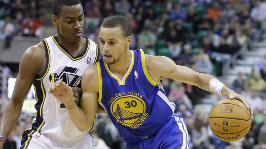 Utah Jazz's Alec Burks, left, defends against Golden State Warriors' Stephen Curry (30) as he drives in the second quarter during an NBA basketball game Monday, Nov. 18, 2013, in Salt Lake City. (AP Photo/Rick Bowmer)