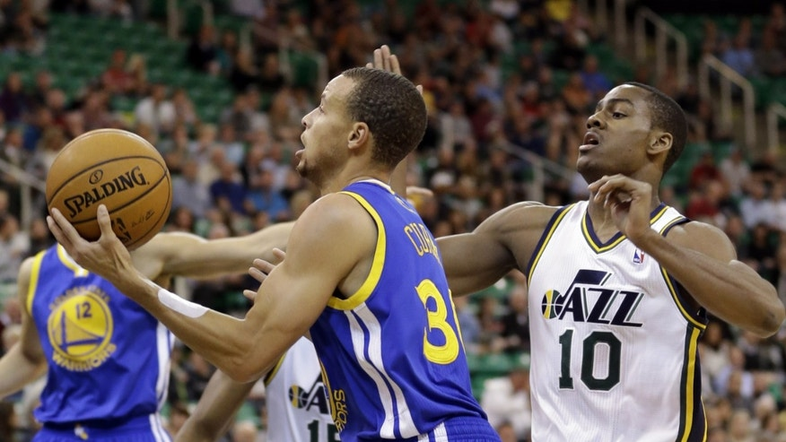 Golden State Warriors' Stephen Curry (30) drives to the basket as Utah Jazz's Alec Burks (10) defends in the first quarter during an NBA basketball game Monday, Nov. 18, 2013, in Salt Lake City. (AP Photo/Rick Bowmer)