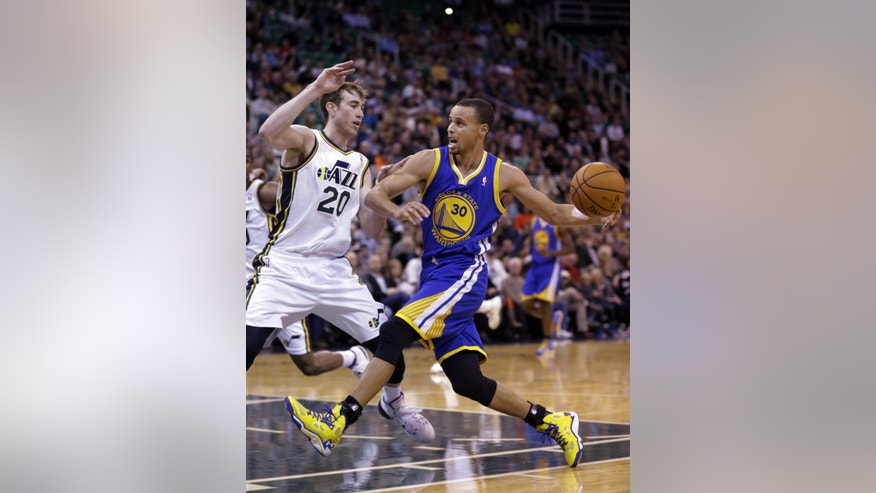 Golden State Warriors' Stephen Curry (30) drives to the basket as Utah Jazz's Gordon Hayward (20) defends in the second quarter during an NBA basketball game Monday, Nov. 18, 2013, in Salt Lake City. (AP Photo/Rick Bowmer)