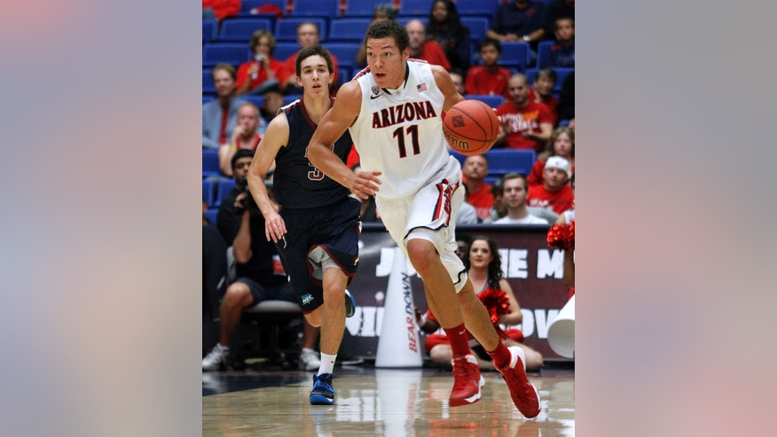 Arizona's Aaron Gordon (11) dribbles the ball away from Fairleigh Dickinson's Matt MacDonald (3) in the first half of an college NCAA basketball game, Monday, Nov. 18, 2013 in Tucson, Ariz. This is in the first round of the NIT. (AP Photo/John Miller)