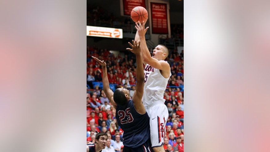 Arizona's Kaleb Tarczewski (35) shoots for two over the defense of Fairleigh Dickinson's Scooter Gillette (25) in the first half of an college NCAA basketball game, Monday, Nov. 18, 2013 in Tucson, Ariz. This is in the first round of the NIT. (AP Photo/John Miller)